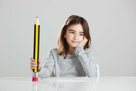 Beautiful little girl in a desk playing with a big pencil, against a gray background Stock Photo - 16126430