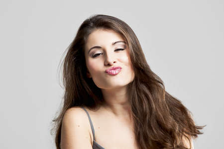 Studio portrait of a beautiful young woman sending a big kiss Stock Photo - 16126427
