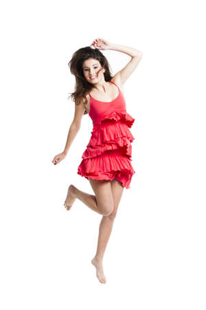 Beautiful woman with a red dress dancing and jumping, isolated on white Stock Photo - 16126402