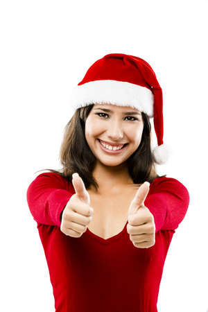 Beautiful asian woman wearing Santas hat with thumbs up, isolated on white photo