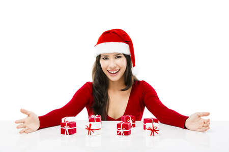 Beautiful asian woman wearing Santas hat with small christmas gifts, isolated on white photo