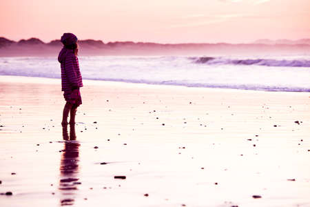 Little girl standing in the beach looking to the ocean photo