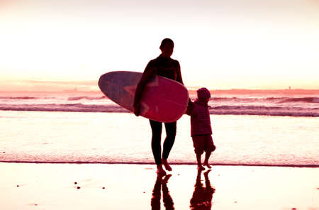Female surfer and her daughter walking in the beach at the sunset photo