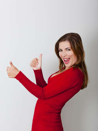 ok sign: Beautiful and happy woman with thumbs up, against a gray wall Stock Photo