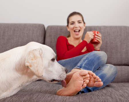 Woman drinking coffee on the sofa with her dog licking her toes photo