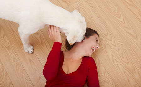 Woman lying on the floor and her dog licking her face photo