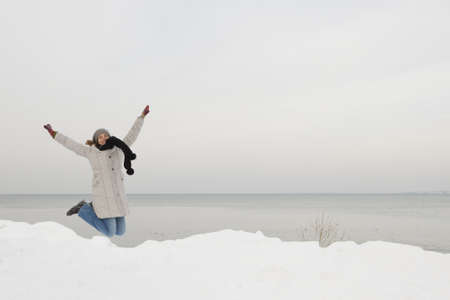 Beautiful woman jumping and enjoying a winter day full of snow photo