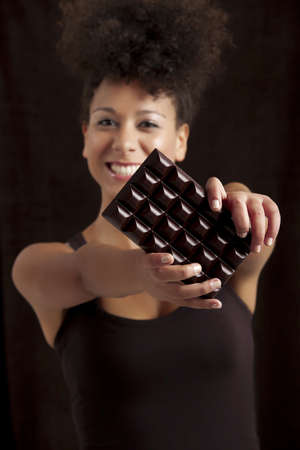 american content: Beautiful african woman holding a huge dark chocolate bar