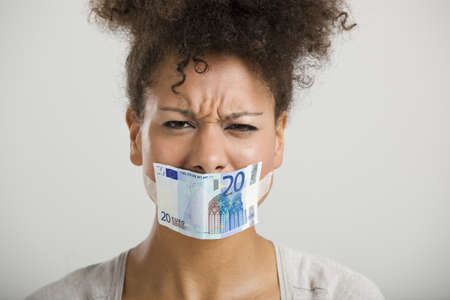 gagged: African woman covering her mouth with a euro banknote, great concept for the global crises