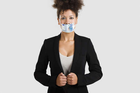 voiceless: Businesswoman covering her mouth with a euro banknote, great concept for the global crises