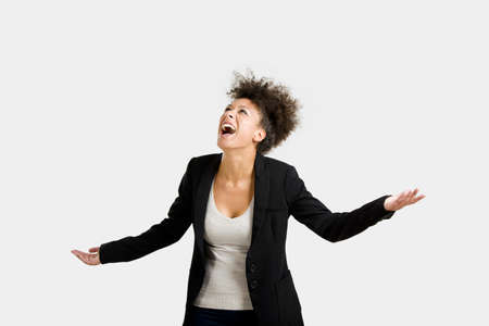 Business woman trying to catch something falling from the sky, isolated over a gray brackground photo