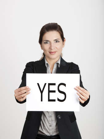 Business young woman showing a paper card with the word YES photo