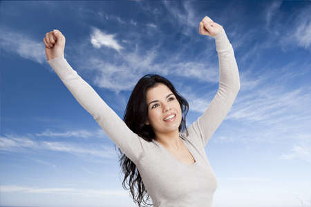 Happy young woman with arms up agains a blue sky Stock Photo - 17041453