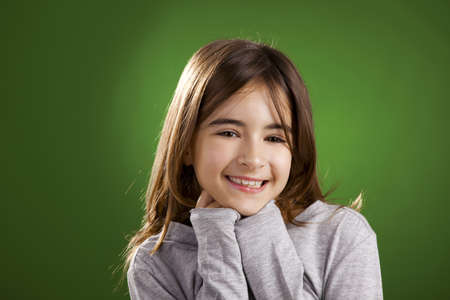 Beautiful child smiling into the camera, against a green background Stock Photo - 17041407