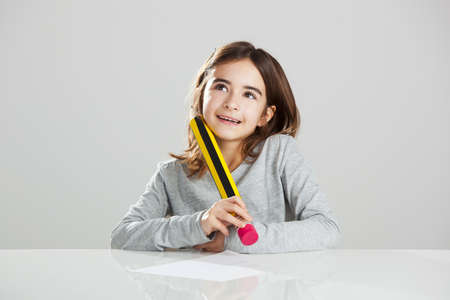 Beautiful little girl in a desk playing with a big pencil, against a gray background Stock Photo - 17041451