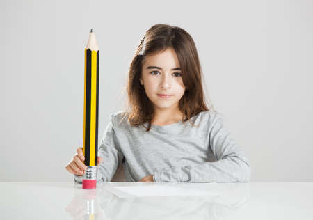 Beautiful little girl in a desk playing with a big pencil, against a gray background Stock Photo - 17041269