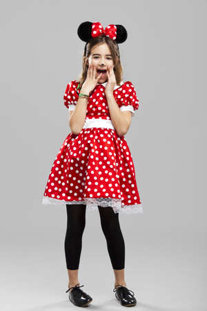 Happy little girl wearing a carnival costume, against a gray background Stock Photo - 17041422
