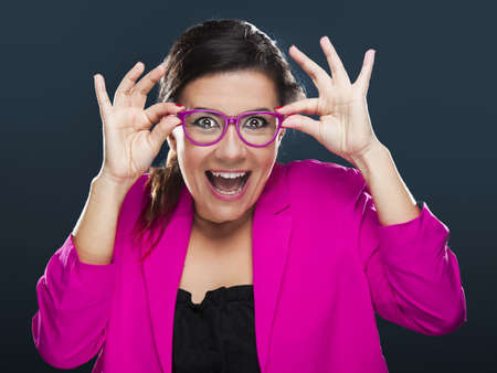 Middle aged woman with a funny face holding her own glasses Stock Photo - 17041450