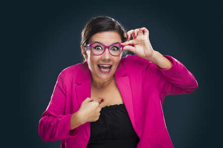 Middle aged woman with a happy face holding her own glasses and pointing to herself Stock Photo - 17041456