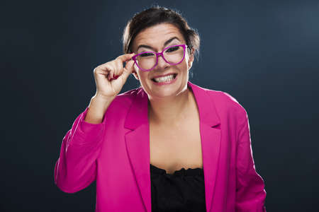 Middle aged woman with a funny face holding her own glasses Stock Photo - 17041411