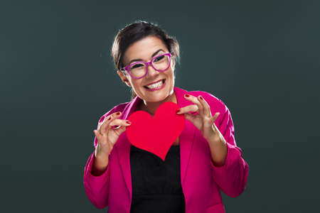 Middle aged woman with a happy face and holding a big red heart card Stock Photo - 17041452