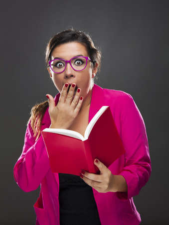Middle aged woman with a astonished expression and holding a red book Stock Photo - 17041462