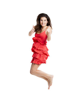 Beautiful woman with a red dress jumping and with thumbs up, isolated on white photo