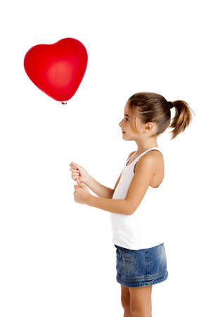 Portrait of a little girl holding and looking to a red balloon, isolated on white background photo