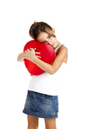 Portrait of a little girl embracing a red balloon, isolated on white background photo