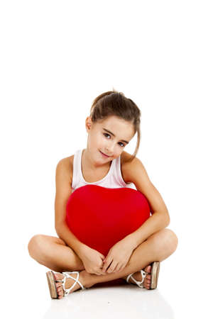 little girl sitting: Portrait of a little girl sitting on floor and embracing a red balloon, isolated on white background