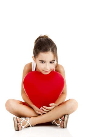 Portrait of a little girl sitting on floor and embracing a red balloon, isolated on white background photo