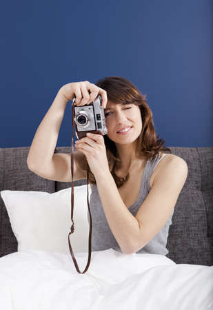 Young girl on the bed holding a photographic camara and shooting Stock Photo - 17241100