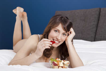 Beautiful and healthy young woman lying on bed and eating fruits Stock Photo - 17241098