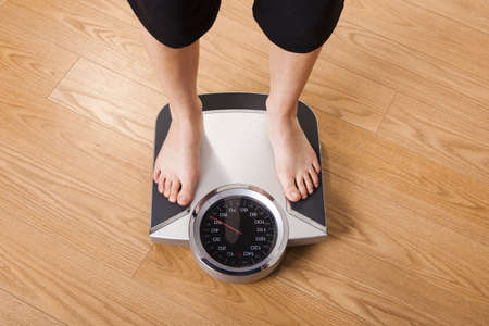 scale weight: Athletic young girl measuring her weight on a scale