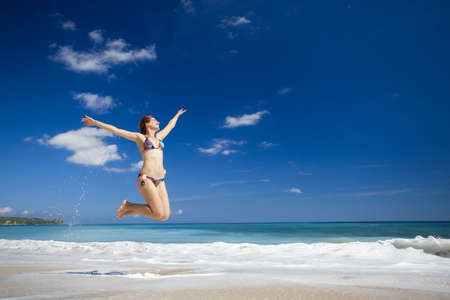 Beautiful and athletic young woman enjoying the summer, jumping in a tropical beach Stock Photo - 17903564
