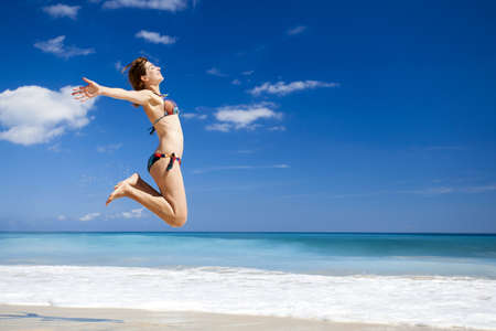 Beautiful and athletic young woman enjoying the summer, jumping in a tropical beach Stock Photo - 17903556