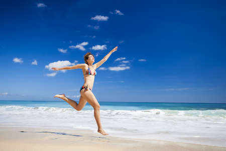 Beautiful and athletic young woman enjoying the summer, jumping in a tropical beach Stock Photo - 17903558