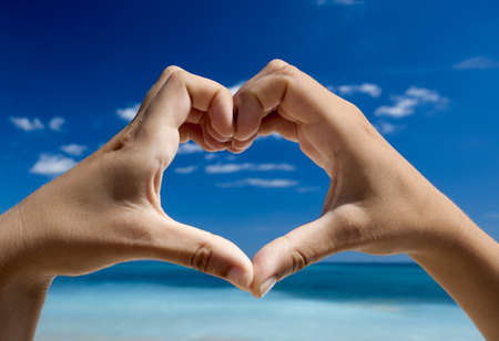 Female hand making a heart shape against a beautiful blue sky Stock Photo - 17903499