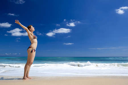 Beautiful young woman with arms open in a tropical beach enjoying the summer Stock Photo - 17903553