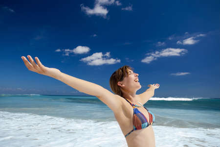 Beautiful young woman with arms open in a tropical beach enjoying the summer Stock Photo - 17903550
