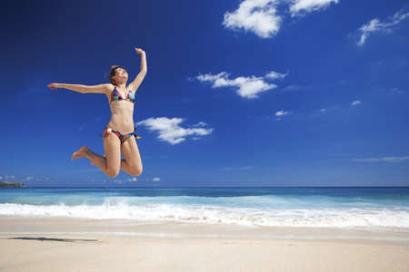 Beautiful and athletic young woman enjoying the summer, jumping in a tropical beach Stock Photo - 17903566