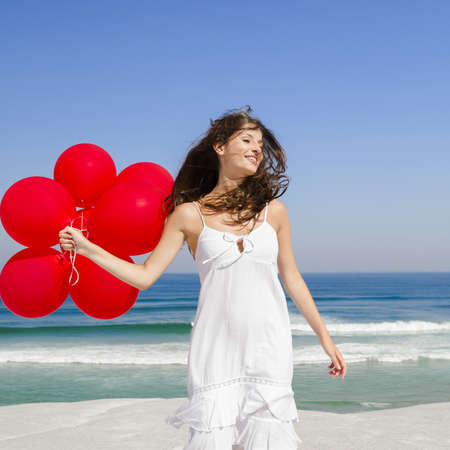 Beautiful girl with red ballons in the beach and wind blowing in the face Stock Photo - 17903505
