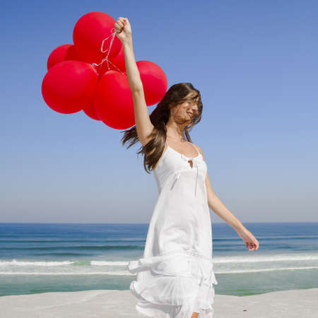 Beautiful girl with red ballons in the beach and wind blowing in the face Stock Photo - 17903518