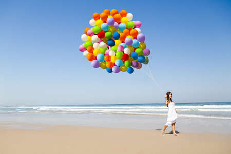 Beautiful girl walking in the beach holding dozens of colored balloons photo
