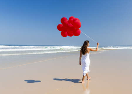 Beautiful girl walking in the beach and holding red balloons Stock Photo - 17903559