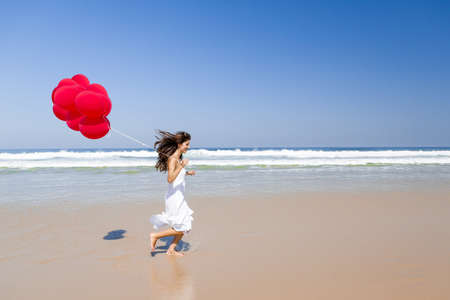 Beautiful girl running in the beach with red ballons in her hand photo