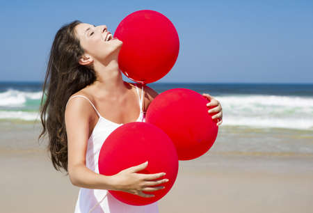 Beautiful girl with red ballons sitting in the beach  Stock Photo - 17903542