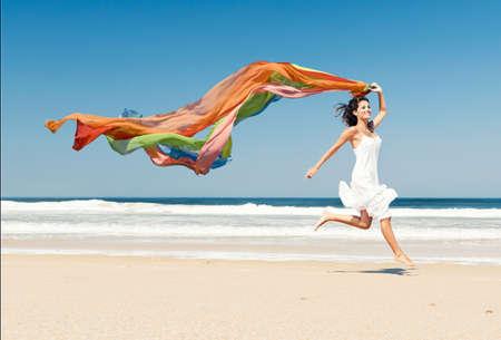 Bella ragazza in spiaggia in esecuzione e in possesso di un pezzo di stoffa colorata
