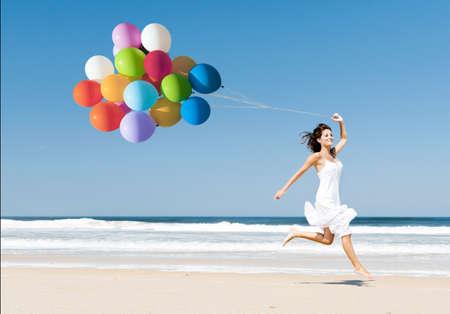 색깔의 풍선을 들고있는 동안 해변에서 산책하는 아름 다운 여자