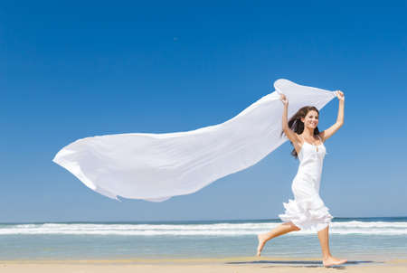 Beautiful girl in the beach running and holding a white piece of fabric Stock Photo